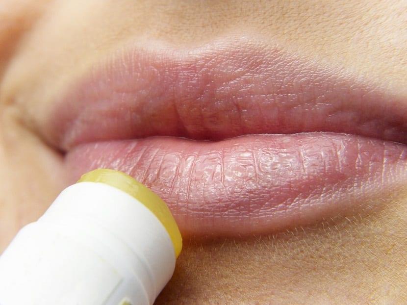 mujer hidratandose los labios secos