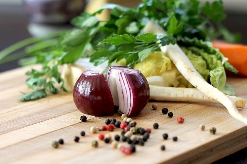 cebolla roja partida por la mitad encima de una tabla de alimentos