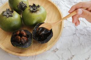frutas del zapote negro dentro de un cuenco de madera