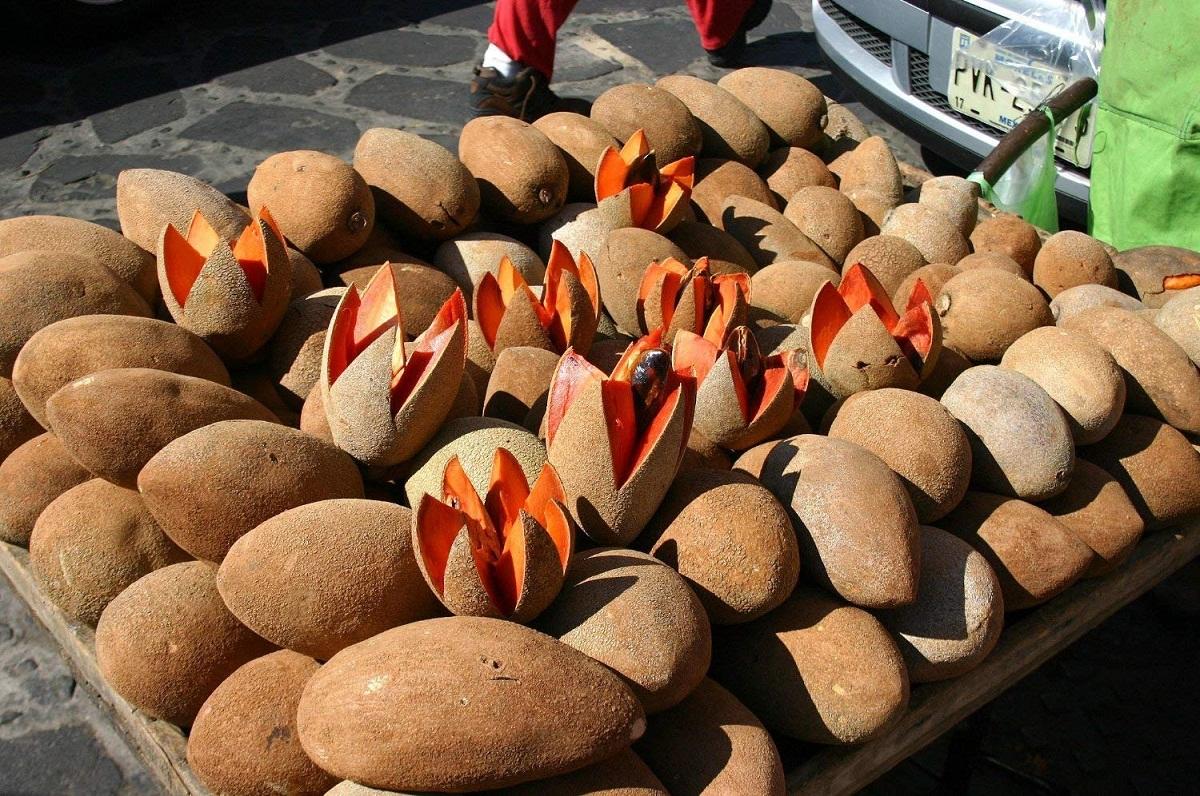 puesto de fruta con Mameys colorados cerrados y abiertos